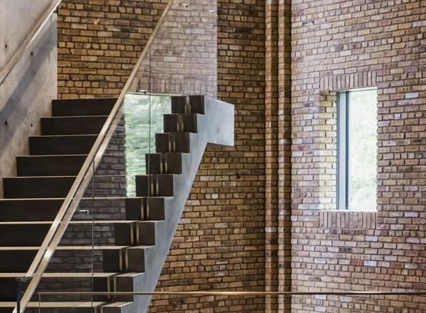Os tijolos à vista se misturam com os corrimãos de vidro e com a escada de concreto (Foto: Jeff Goldberg/ Reprodução)