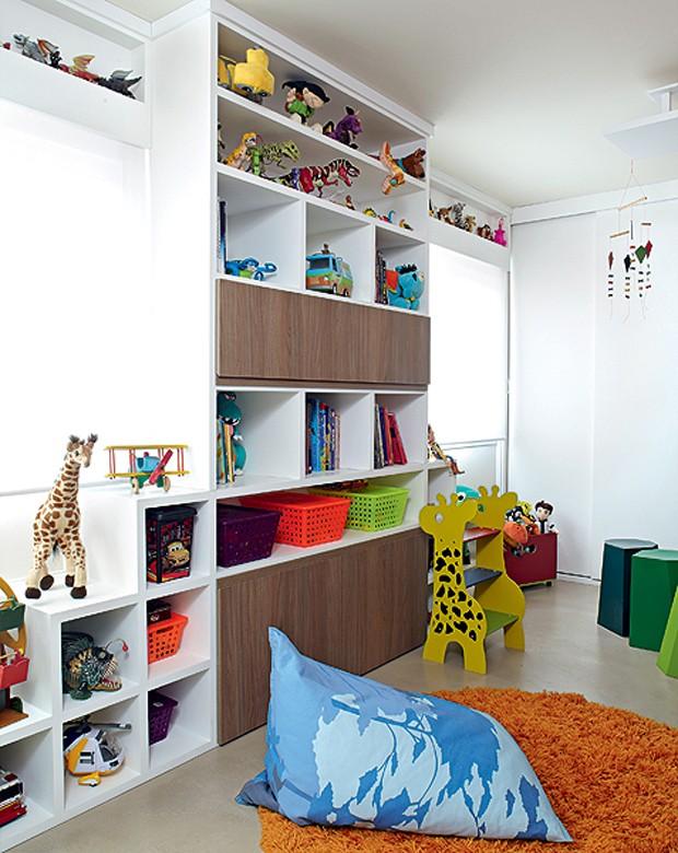 A estante com nichos guarda todos os brinquedos, mas se esvazia facilmente: a escadinha de girafa dá uma mão e uns centímetros a mais, se for o caso. Cestinhos coloridos organizam as miudezas. Projeto do escritório Lovisaro Arquitetura e Design (Foto: Victor Affaro/Casa e Jardim)
