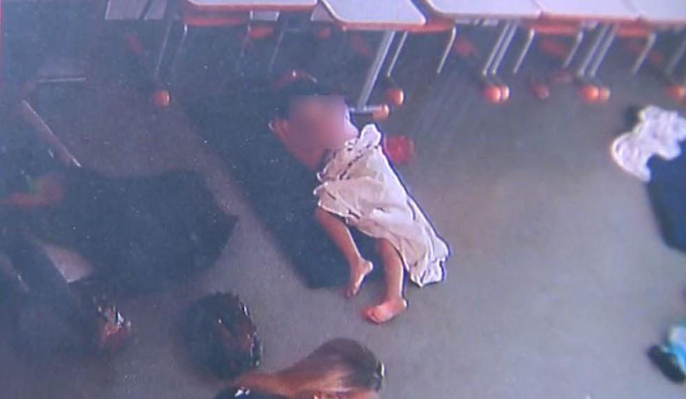 Sentanda no chão, professora tenta segurar aluno dentro de saco de lixo (à esquerda), enquanto menina dorme no colchão ao lado em Restinga, SP (Foto: Câmeras de segurança)