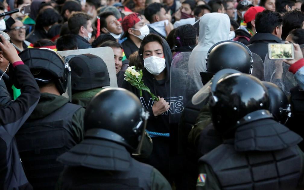 Manifestante segura flores enquanto encara policiais durante protesto em La Paz, na Bolívia, na terça-feira (22) — Foto: Reuters/David Mercado
