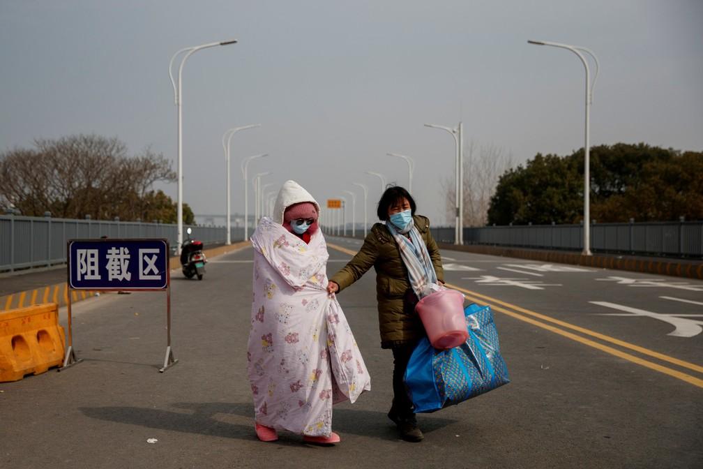 Uma paciente com leucemia e sua mãe, vinda da província de Hubei, cruzam um posto de controle na ponte do rio Jiujiang Yangtze em Jiujiang, província de Jiangxi, na China, em 1º de fevereiro  — Foto: Thomas Peter/Reuters