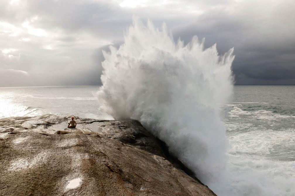9 de agosto - Homem observa o mar no momento em que uma onda explode ao seu lado lado devido à forte ressaca no Arpoador, Zona Sul do Rio de Janeiro (Foto: André Melo/Futura Press/Estadão Conteúdo)