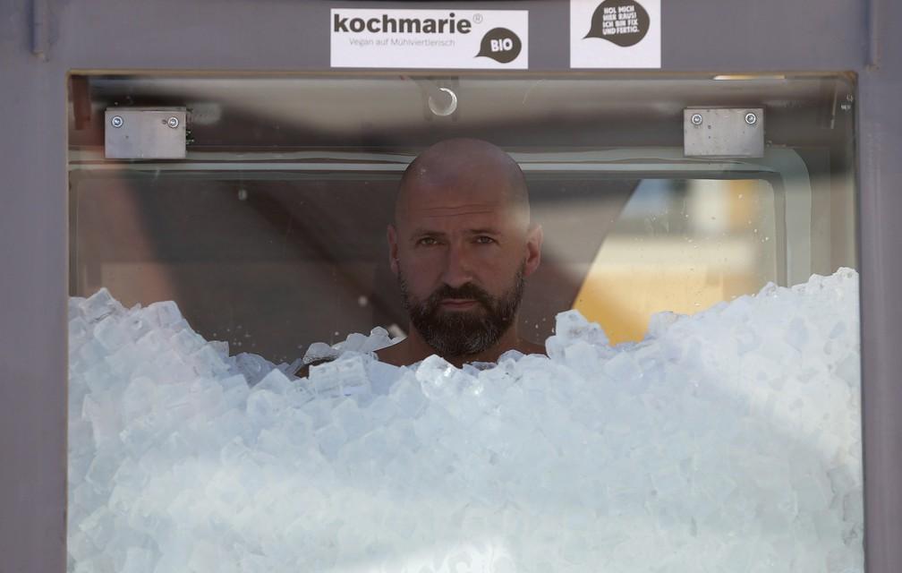 O nadador austríaco Josef Koeberl é visto dentro de uma cabine de vidro cheia de gelo tentando quebrar o recorde mundial, em Melk, Áustria  — Foto: Ronald Zak/AP
