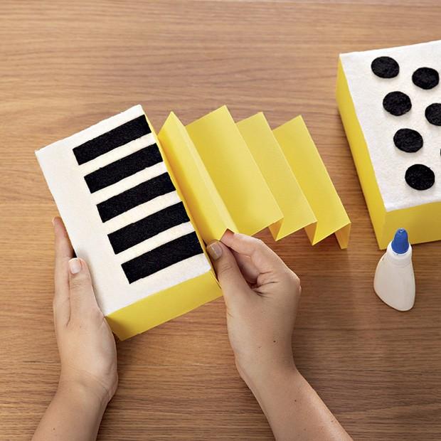 5. Recorte o papel amarelo (14 cm x 30 cm) e forme um leque com dobras com 4 cm de distância. Cole as extremidades nas partes internas das caixas. (Foto: Bruno Marçal / Editora Globo)