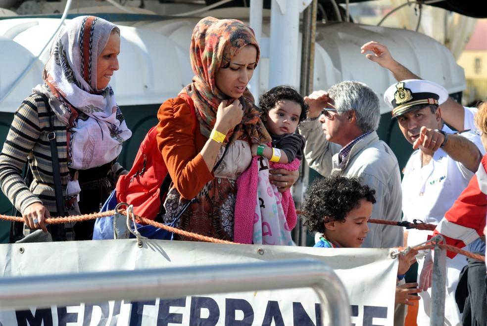 -  Uma mulher segura um bebê enquanto desembarca após ser resgatada do barco  Aquarius  em Palermo, na Itália  Foto: Alessandro Fucarini/AFP