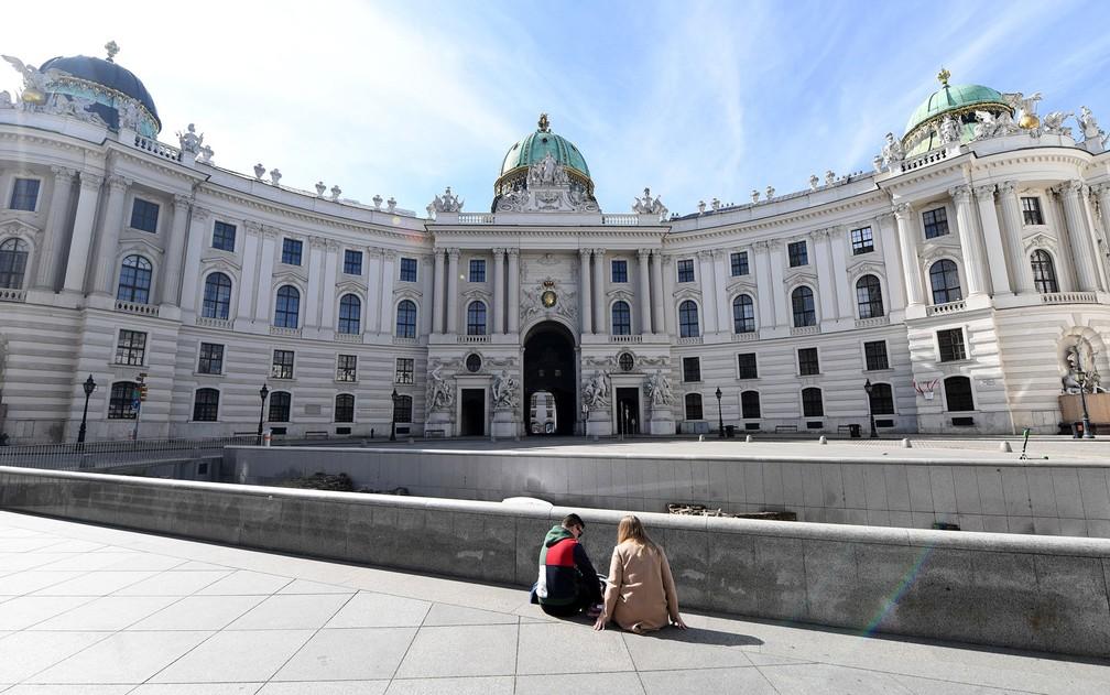 Em Viena, duas pessoas sentam em uma praça vazia. O governo austríaco proibiu reuniões de mais de cinco pessoas  — Foto: Helmut Fohringer/APA/AFP