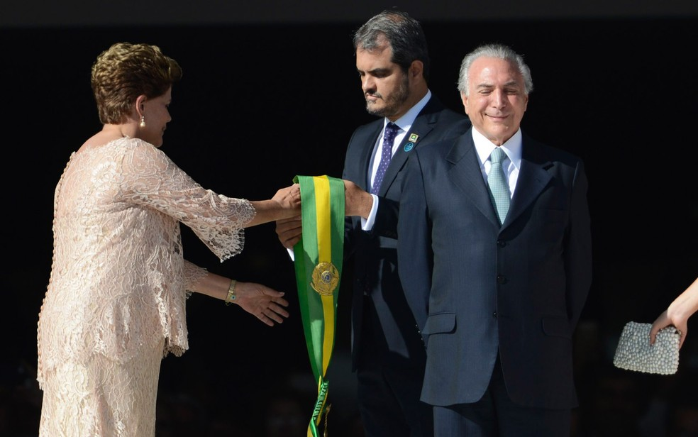 A então presidente Dilma Rousseff recebe a faixa de presidente ao lado do vice Michel Temer na cerimônia de posse em 2015 (Foto: Marcelo Camargo/Agência Brasil)