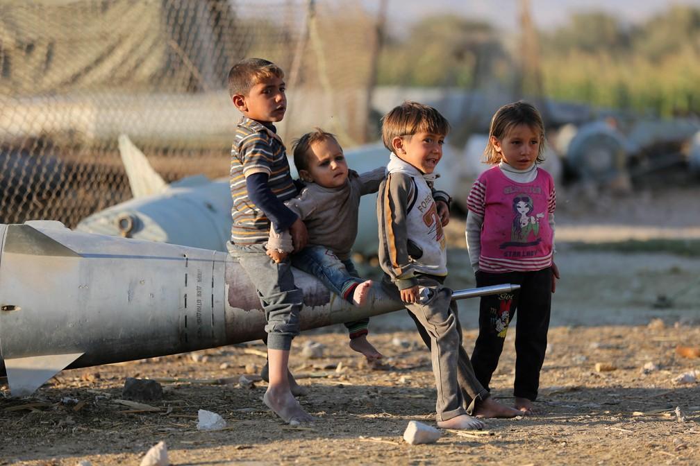 Crianças brincam nesta quarta-feira (25) com um míssil abandonado no campo de deslocados Ash'ari, na área de Ghouta Oriental (Foto: AFP/ Amer Almohibany)