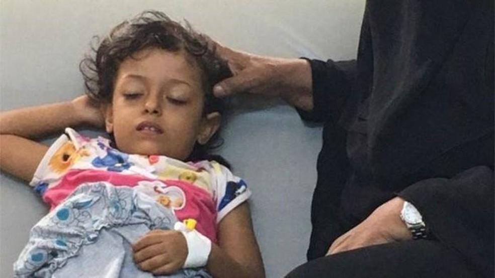 Malak, cujo nome quer dizer 'anjo', está fraca demais para sustentar sua cabeça - então a mãe faz isso para ela (Foto: BBC)