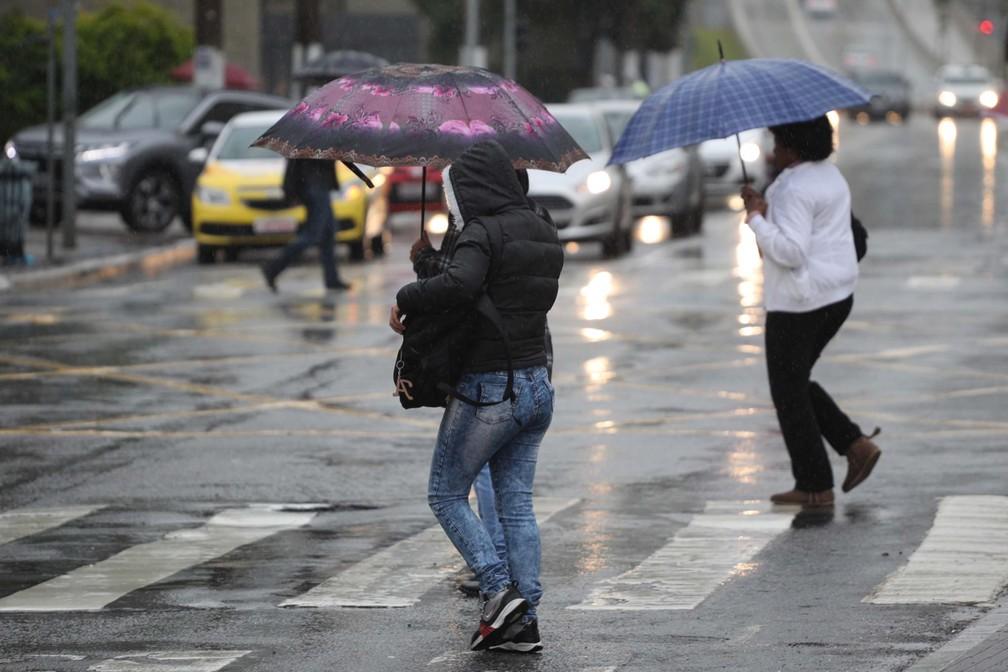 Pedestres se protegem da chuva na Avenida Santo Amaro, na Zona Sul de São Paulo, nesta sexta (5) — Foto: Renato S. Cerqueira/Estadão Conteúdo