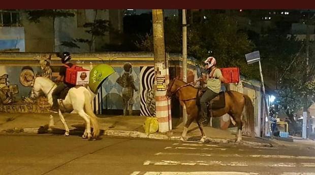Cavaleiros fazem entrega de bebidas no bairro de Pinheiros, em São Paulo (Foto: Estadão Conteúdo)