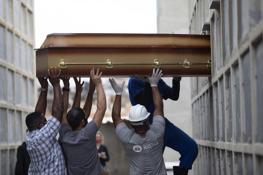 Corpo de mulher que morreu por complicações relacionadas à Covid-19 é colocado em nicho por funcionários e parentes no cemitério de Inahuma, no Rio de Janeiro, em 13 de abril de 2021 — Foto: Silvia Izquierdo/AP
