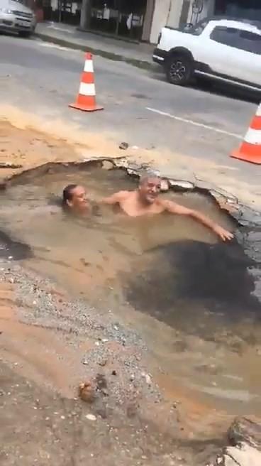 Vídeo mostra moradores 'tomando banho' em buraco ocasionado por vazamento subterrâneo em Divinópolis - Notícias - Plantão Diário