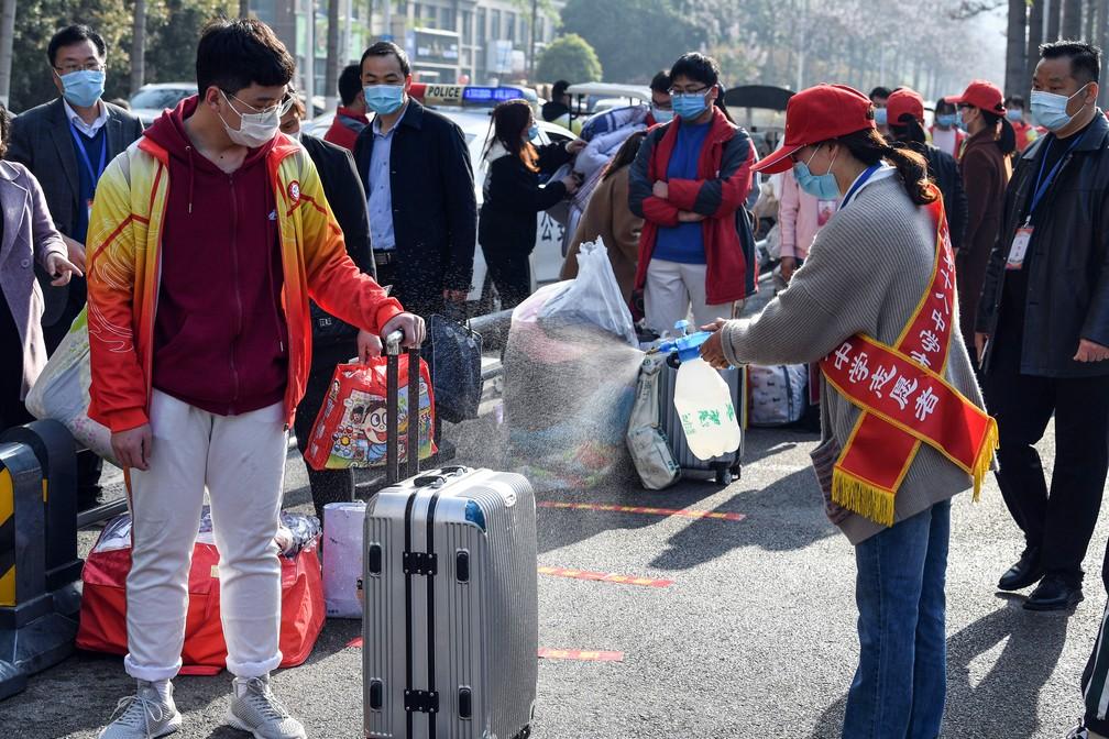 7 de abril - Voluntária utiliza spray desinfetante em bagagem de um aluno em Bozhou, na província de Anhui, no leste da China, nesta terça-feira (7)  — Foto: AFP