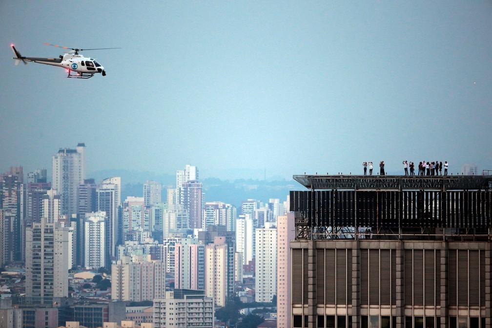 Observadores aguardam nascer da lua no topo de prédio em São Paulo; na imagem, GloboCop da TV Globo (Foto: Paulo Whitaker/Reuters)