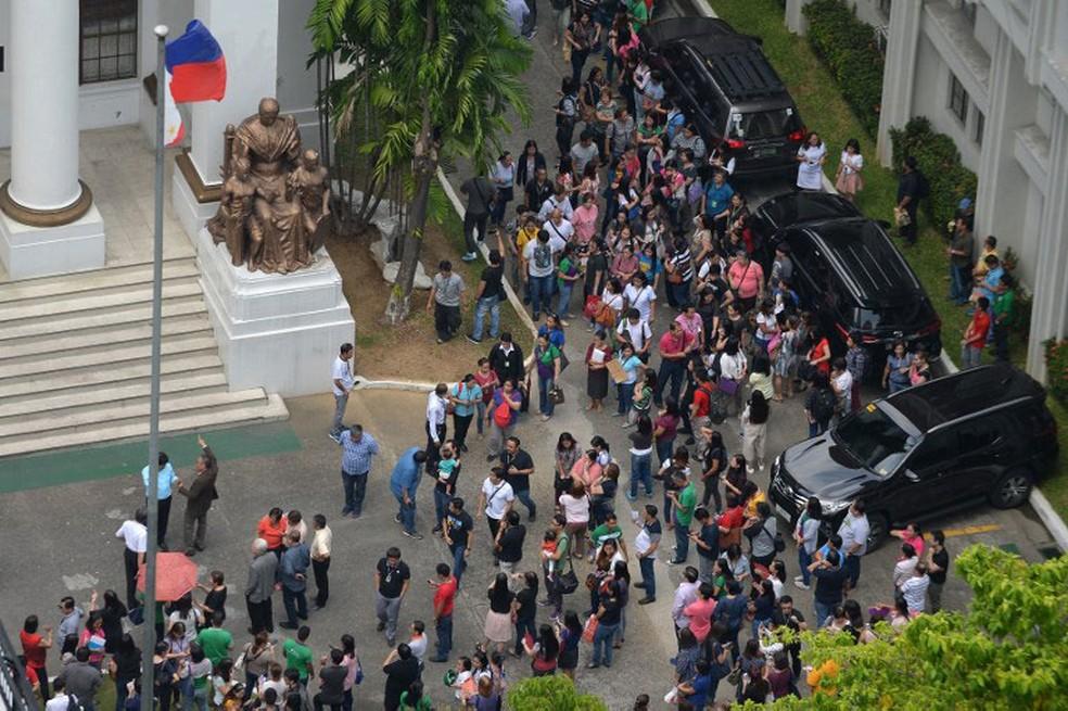 Funcionários deixam tribunal após terremoto ser sentido em Manila, nas Filipinas, nesta sexta-feira (11)  (Foto: Ted Aljibe / AFP)
