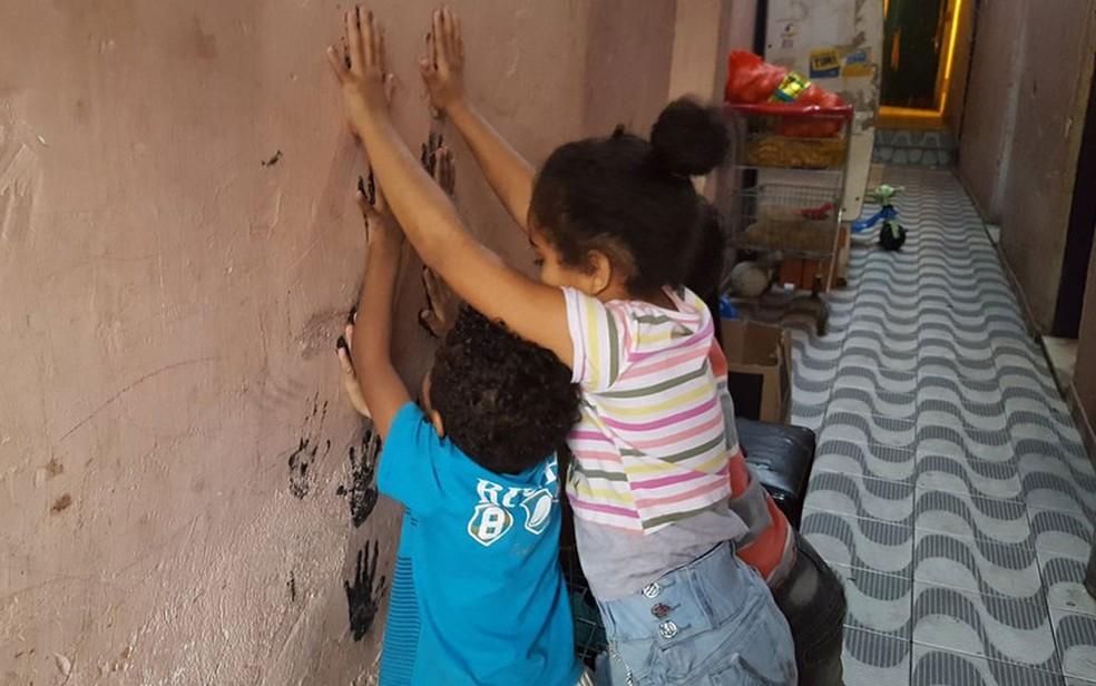 Filhos de Renata brincam no corredor de cortiço onde moram no centro de SP  (Foto: Felipe Souza/BBC Brasil)