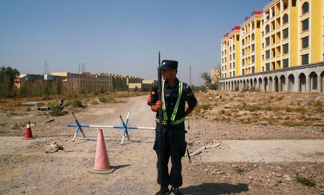 Policial chinês próximo ao que é oficialmente chamado de centros vocacionais em Yining, em Xinjiang