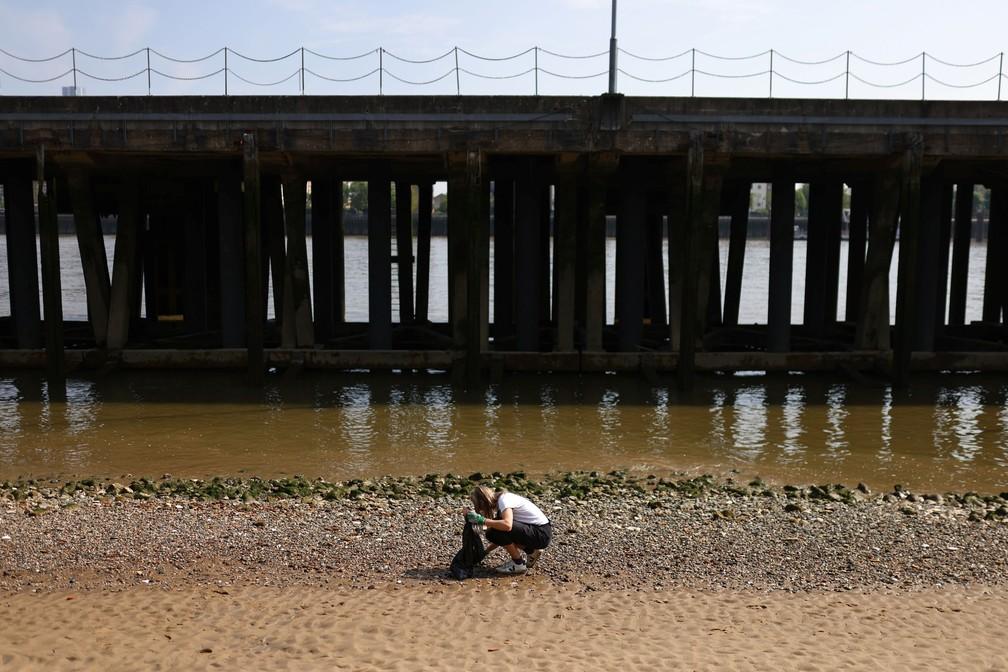 Flora Blathwayt coleta plástico nas margens do rio Tâmisa — Foto: Tom Nicholson/Reuters