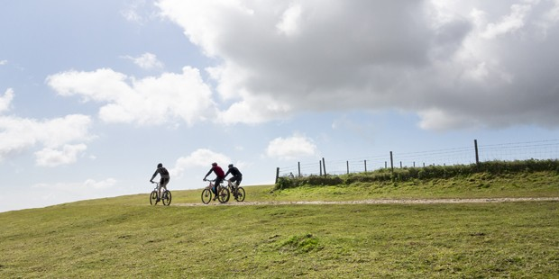 """""""Three mountain cyclists almost silhouetted on a ridge of a hill in the South Downs, England, UK while cycling the South West Way"""" (Foto: Getty Images/iStockphoto)"""