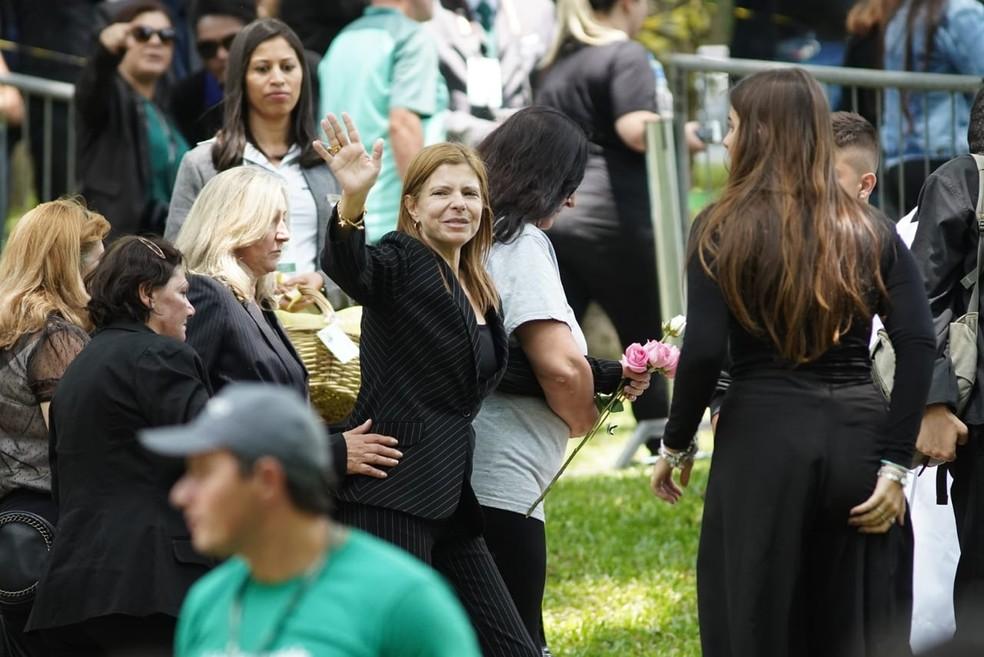 Viúva de Gugu acena para o pública agradecendo apoio durante enterro do companheiro. — Foto: Marcelo Brandt/G1