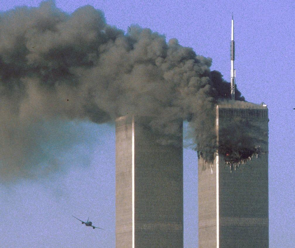 Segundos antes, avião do voo 175 da United Airlines é visto se aproximando da Torre Sul do WTC, em Nova York, enquanto a Torre Norte pega fogo, durante os ataques terroristas do 11 de Setembro — Foto: Sean Adair/Reuters/Arquivo