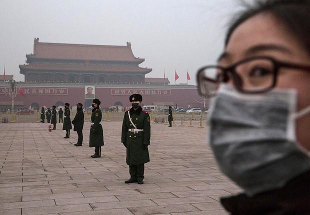 Jovem chinesa visita Pequim em dia de alto nível de poluição, em que habitantes saíram às ruas com máscaras para se proteger (Foto: Kevin Frayer/Getty Images)