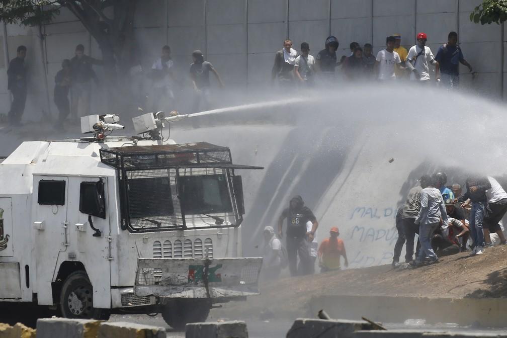 Um canhão de água da Guarda Nacional Bolivariana dispersa os oponentes ao presidente da Venezuela, Nicolás Maduro, em Caracas, na Venezuela — Foto: Ariana Cubillos/AP