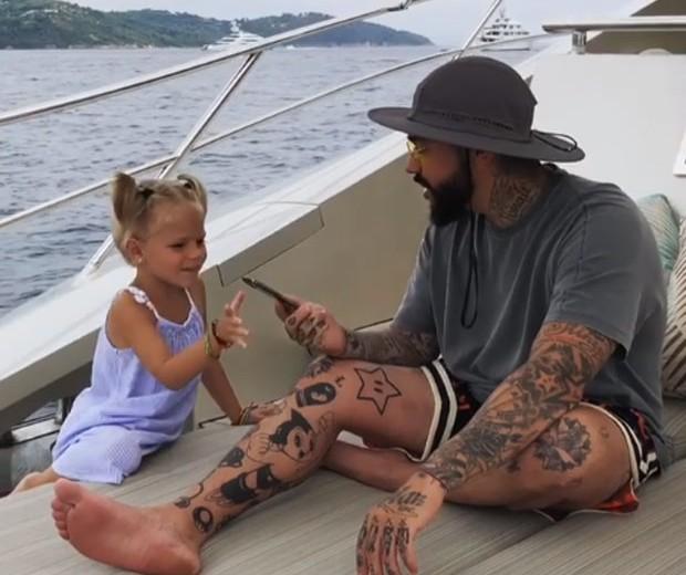 O momento em que a menina pega o celular das mãos do pai (Foto: Reprodução / Instagram)