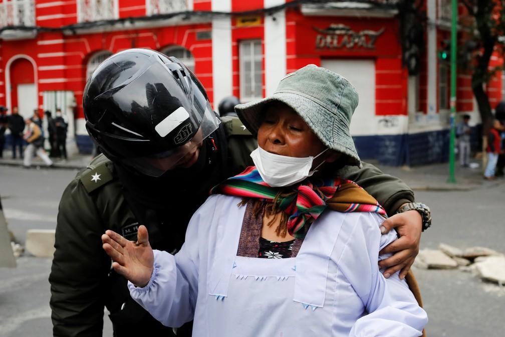 Policial retira mulher de região de confronto entre forças de segurança e manifestantes em La Paz, na Bolívia, nesta quarta-feira (13) — Foto: Marco Bello/Reuters