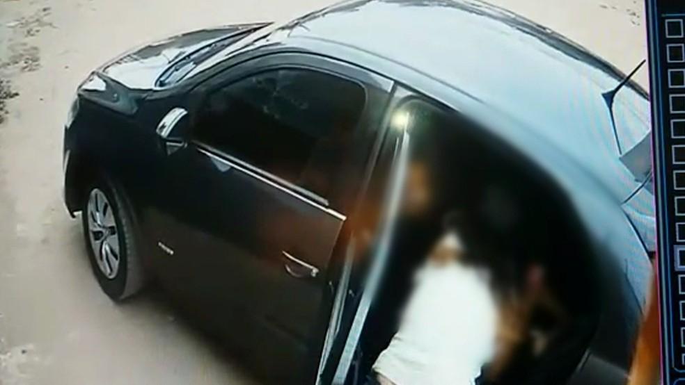 Bandidos já estavam dentro do carro quando mãe tenta tirar criança do veículo (Foto: Reprodução/TV Globo)