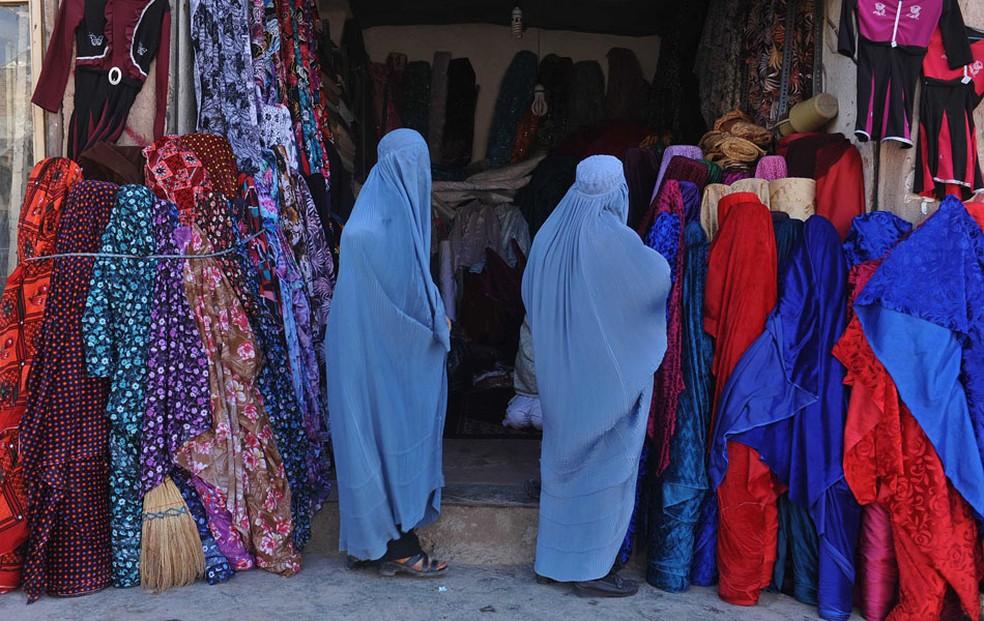 Mulheres afegãs vestidas de burca olham roupas em frente de uma loja de roupas em Herat em 2012. — Foto: Aref Karimi/AFP