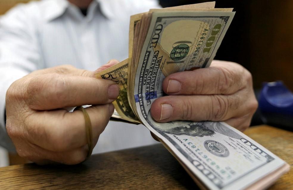 Homem conta notas de dólar em casa de câmbio no Cairo, Egito. — Foto: Reuters