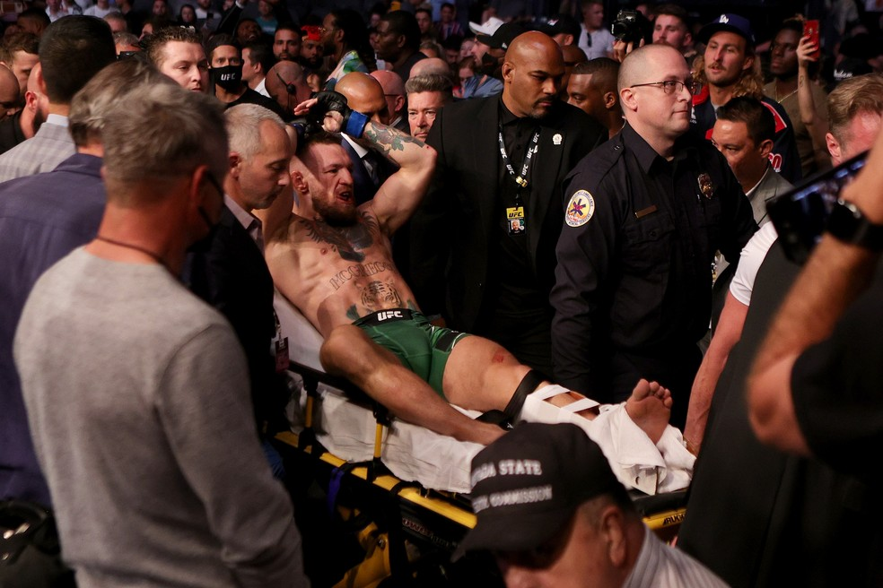 Conor McGregor deixa o octógono do UFC 264 de maca após fraturar o tornozelo — Foto: Getty Images