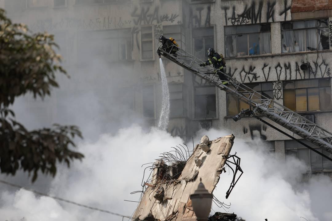 Bombeiros usam água para resfriar os escombros
