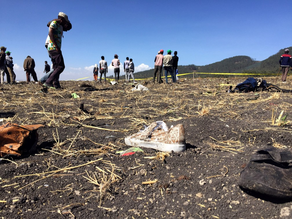 Pessoas caminham sobre o local de acidente aéreo na Etiópia — Foto: Tiksa Negeri/Reuters