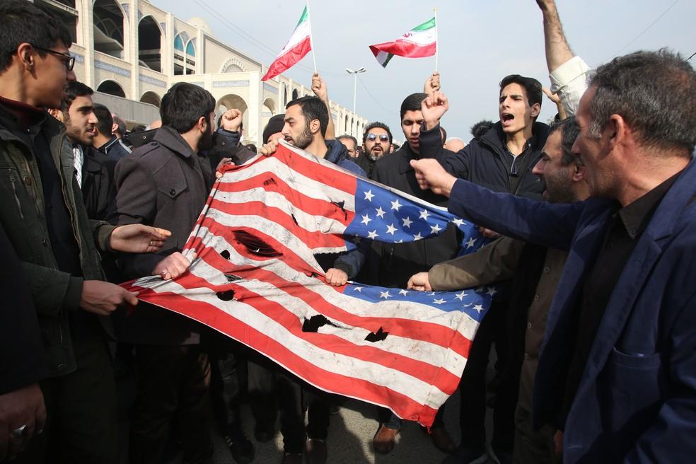 Iranianos destroem uma bandeira americana durante protesto em Teerã no dia 3 de janeiro pela morte do general Qassem Soleimani. — Foto: Atta Kenare / AFP