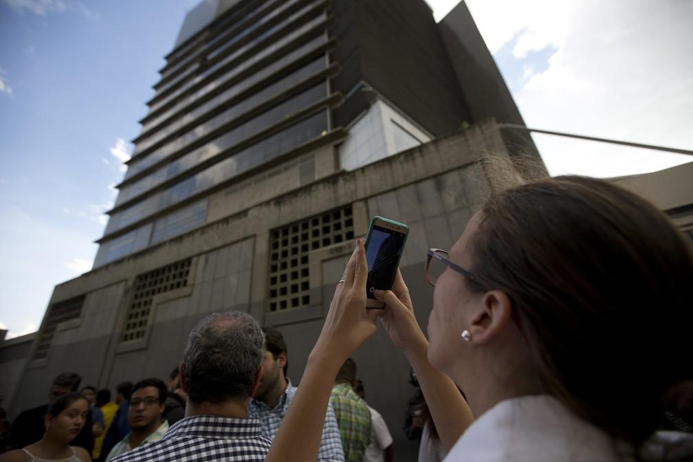 Manuela Bolivar, advogada e membro do partido de oposição Primeiro Justicia, tira fotos do prédio da Sebin em Caracas — Foto: Fernando Llano/AP Photo