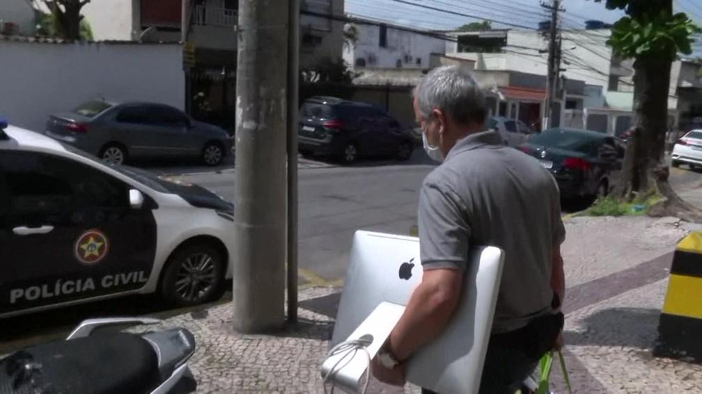 Policiais apreenderam computadores e papéis que possam ajudar nas investigações sobre suposto esquema formado por funcionários públicos para atrapalhar o trabalho da imprensa — Foto: Reprodução/ TV Globo