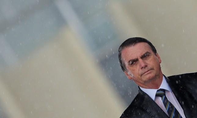 Presidente Jair Bolsonaro sob chuva durante solenidade militar em Brasília