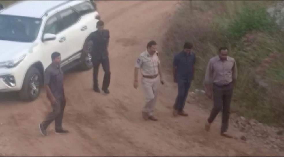 Frame mostra momento em que suspeitos, acompanhados da polícia, chegam nesta sexta-feira (6) para reconstituição de estupro e morte de veterinária em Hyderabad, na Índia  — Foto: ANI/via Reuters TV