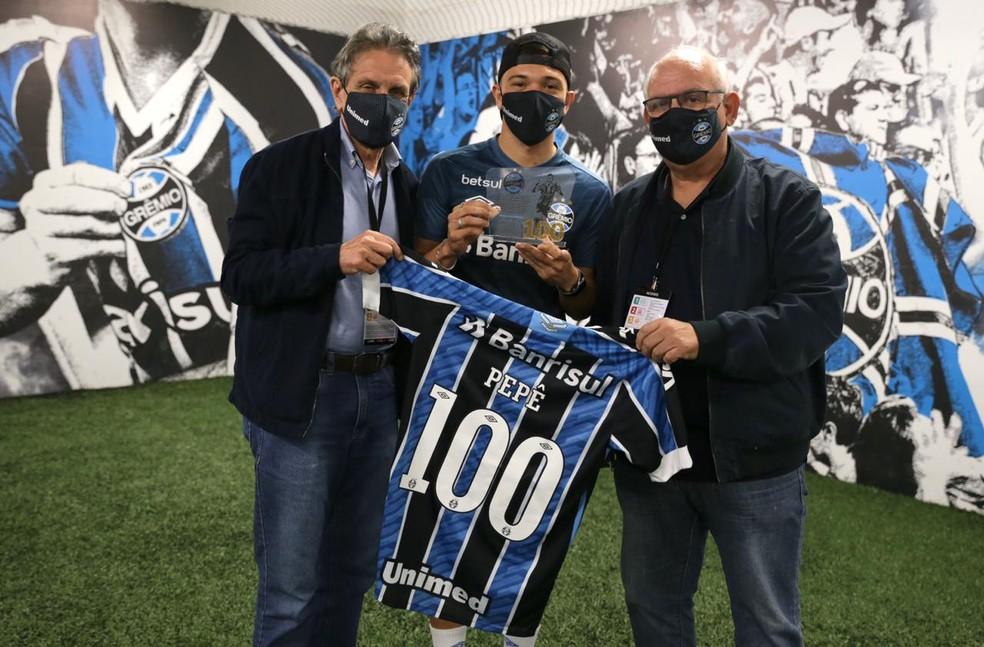 Pepê recebe homenagem pelos 100 jogos do vice de futebol Paulo Luz e do presidente Romildo Bolzan Jr. — Foto: Grêmio FBPA/Divulgação