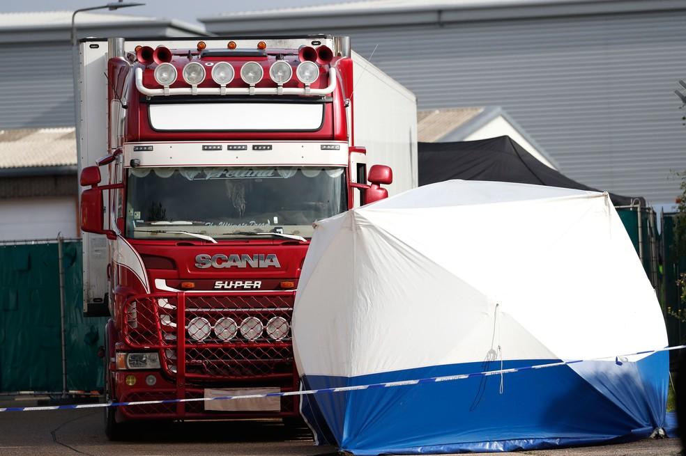 Polícia montou barraca em frente ao caminhão onde foram encontrados 39 corpos no sul da Inglaterra, nessa quarta-feira (23)  — Foto: Alastair Grant/AP