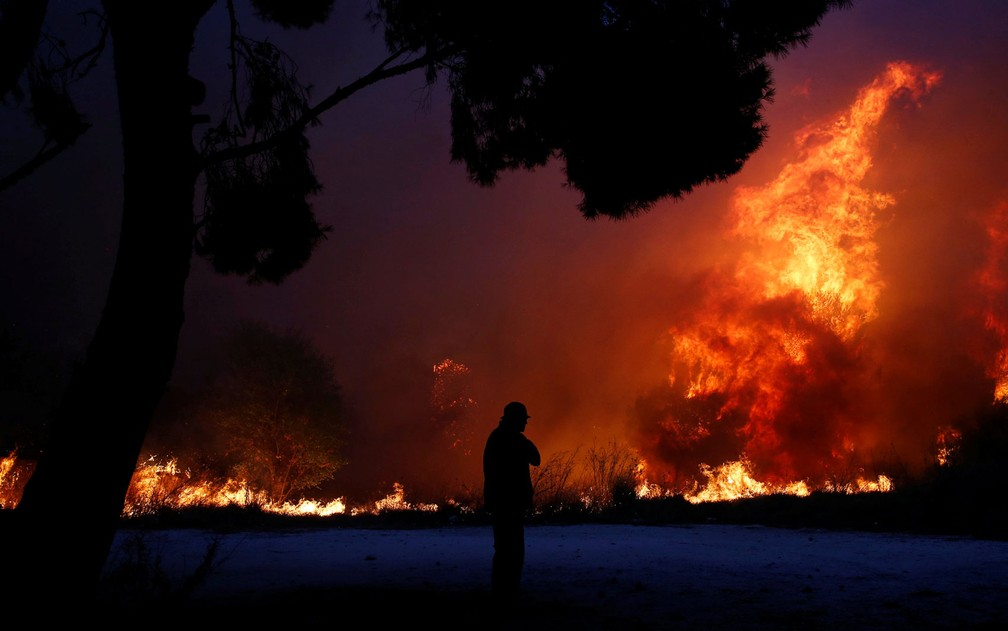 Homem observa chamas em incêndio florestal na cidade de Rafina, perto de Atenas, na Grécia (Foto: Costas Baltas / Reuters)