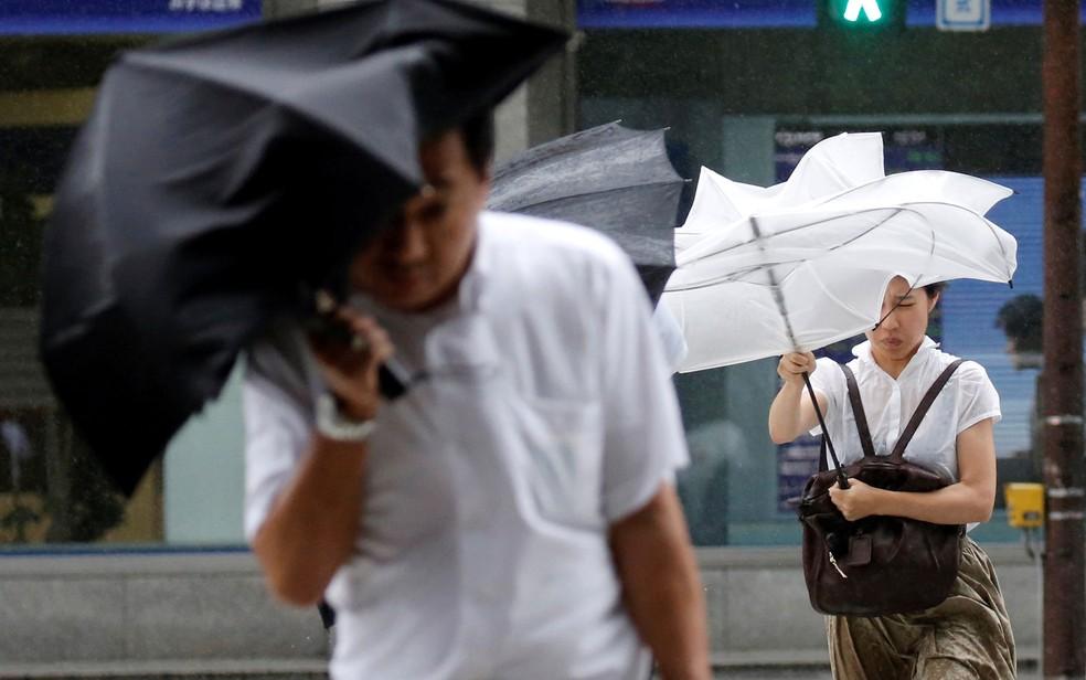 -  Japoneses lutam com a sombrinha na rua durante vendaval provocado pela chegada do tufão Shanshan em Tóquio, na quarta-feira  8   Foto: Reuters/Toru H