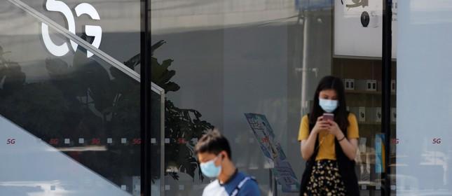 Uma mulher utiliza um smartphone com tecnologia 5G em Pequim, na China