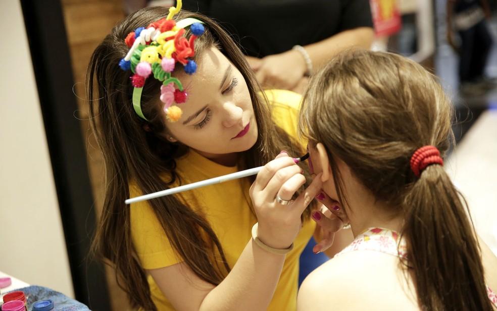 Mulher faz pintura de rosto em menina durante programação infantil no JK Shopping, em Brasília — Foto: Telmo Ximenes/Divulgação