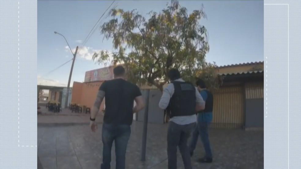 Policiais ao abordar casa onde produtos eram escondidos no DF (Foto: Reprodução/TV Globo)