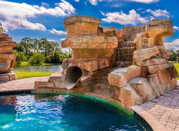 Um tobogã fica escondido entre as pedras artificiais (Foto: Treasure Coast Sotheby's International Realty/ Reprodução)