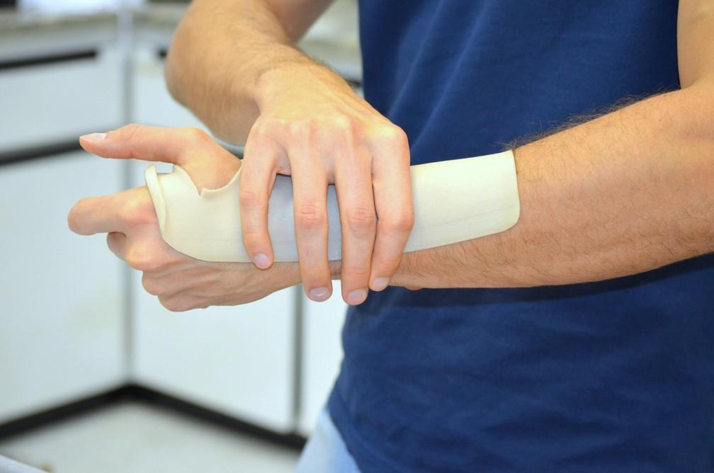 Chapa é colocada na água e deve ser encaixada no braço para criar o molde do  (Foto: Thayná Cunha/G1)
